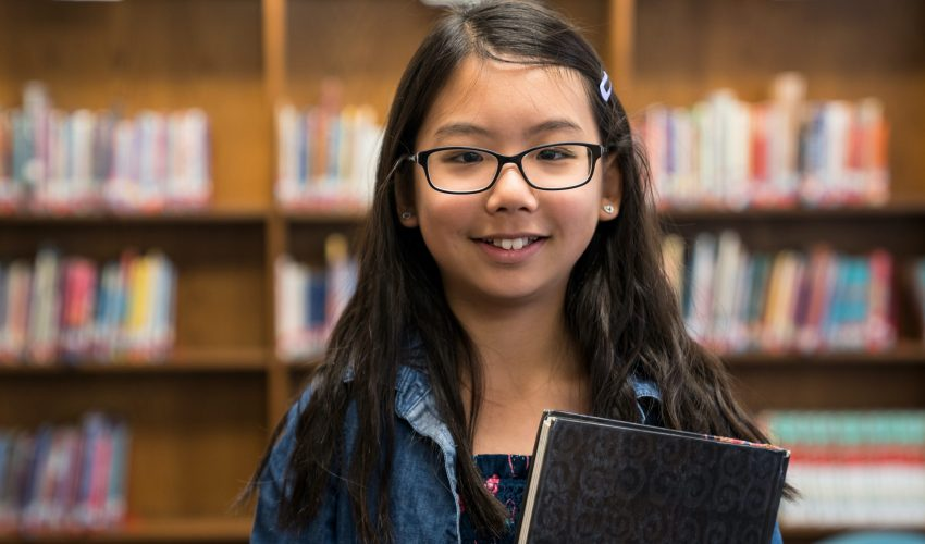 Back to school concept with a teenage Asian girl with eyeglasses standing with books in the school library
